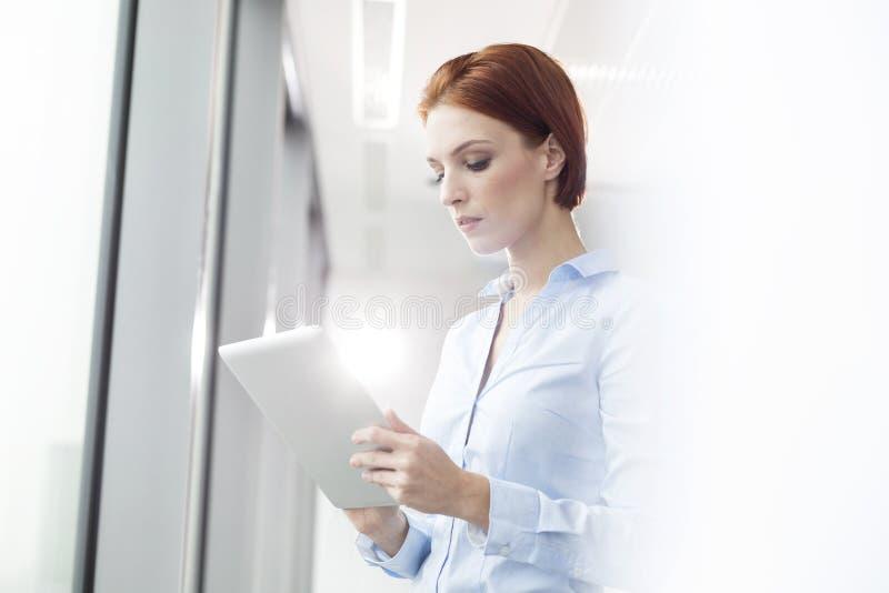 Jonge onderneemster die digitale tablet gebruiken terwijl status in bestuurskamer op kantoor royalty-vrije stock fotografie