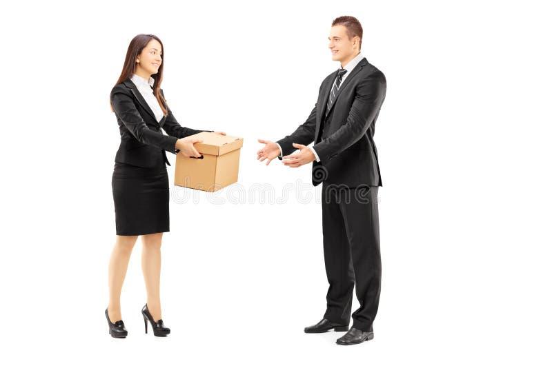 Jonge onderneemster die een doos geven aan haar mannelijke collega stock foto