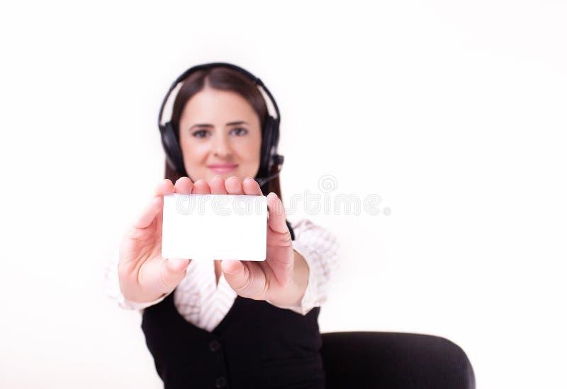 Jonge onderneemster die een hoofdtelefoon dragen die een leeg wit standhouden stock foto