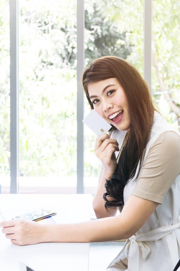 Jonge onderneemster die en over het projectwerk op kantoor glimlachen denken stock foto