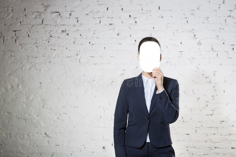 Jonge onderneemster die gezicht behandelen met leeg document tegen witte bakstenen muur op kantoor royalty-vrije stock afbeelding