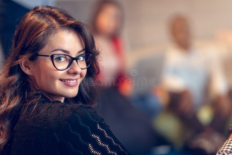 Jonge onderneemster die glazen dragen die vol vertrouwen terwijl status in een bureau met collega's die in werken glimlachen royalty-vrije stock afbeelding