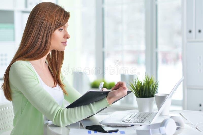 Jonge onderneemster die het scherm van laptop en het schrijven informatie in klembord bekijken stock afbeelding