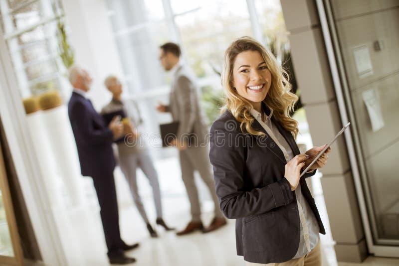 Jonge onderneemster die met tablet in bureau gebruiken terwijl andere busi stock afbeeldingen