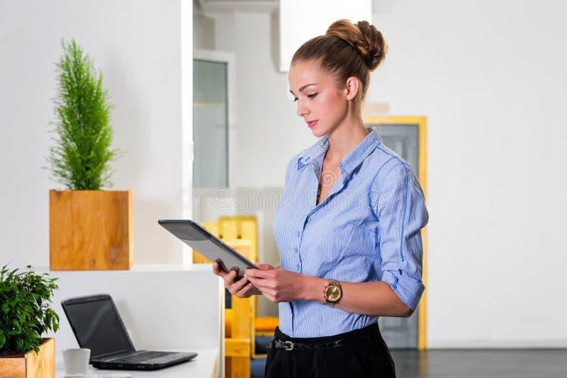 Jonge onderneemster die in modern helder bureau de tablet met een lijst van taken houden Bedrijfsconcept het bureauwerk stock afbeeldingen