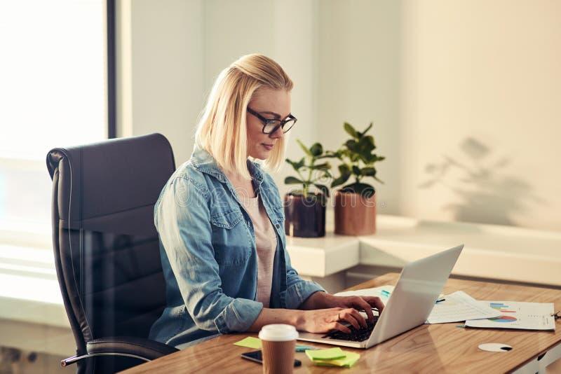 Jonge onderneemster die online bij haar bureau in een bureau werkt stock foto