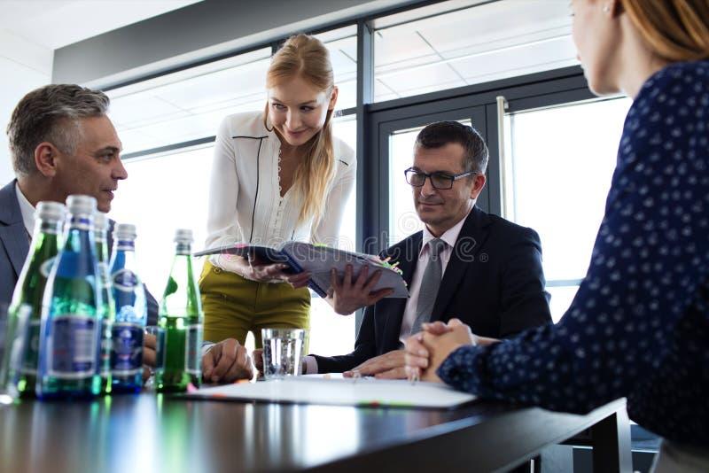 Jonge onderneemster die project tonen aan zakenman tijdens vergadering in bureau stock fotografie