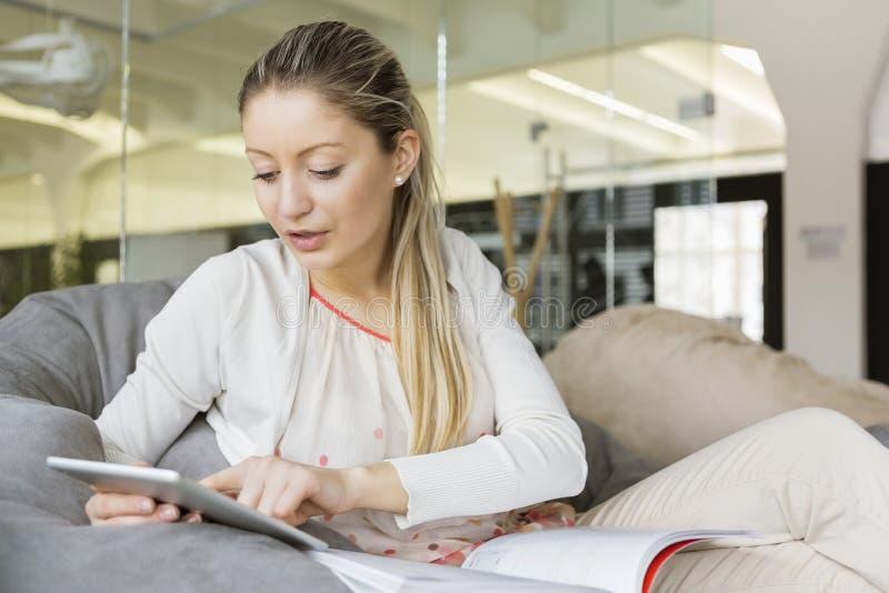 Jonge onderneemster die tabletpc in bureau met behulp van royalty-vrije stock foto