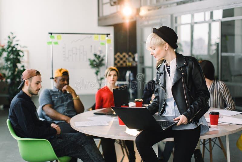 Jonge onderneemster die in vrijetijdskleding bij bureau werken, die laptop computer met behulp van Diverse Groep BedrijfsMensen stock foto