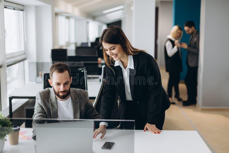Jonge onderneemster en zakenman die samen met beambten aan achtergrond in modern bureau werken stock afbeelding