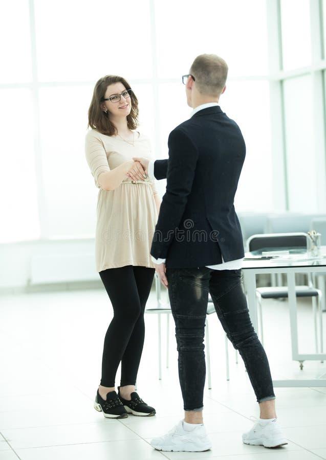 Jonge onderneemster het schudden handen met haar partner stock foto's