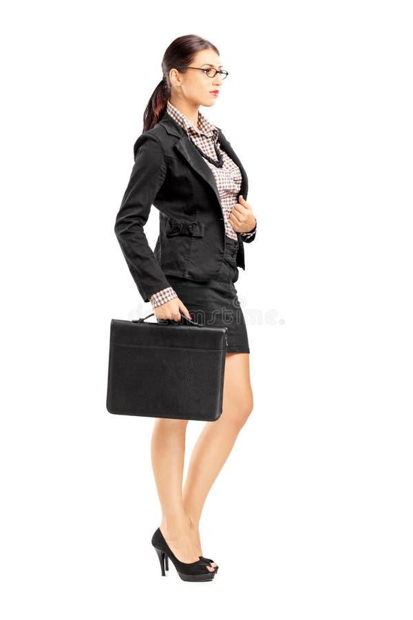 Jonge onderneemster in kostuum het stellen met een aktentas in haar hand stock fotografie
