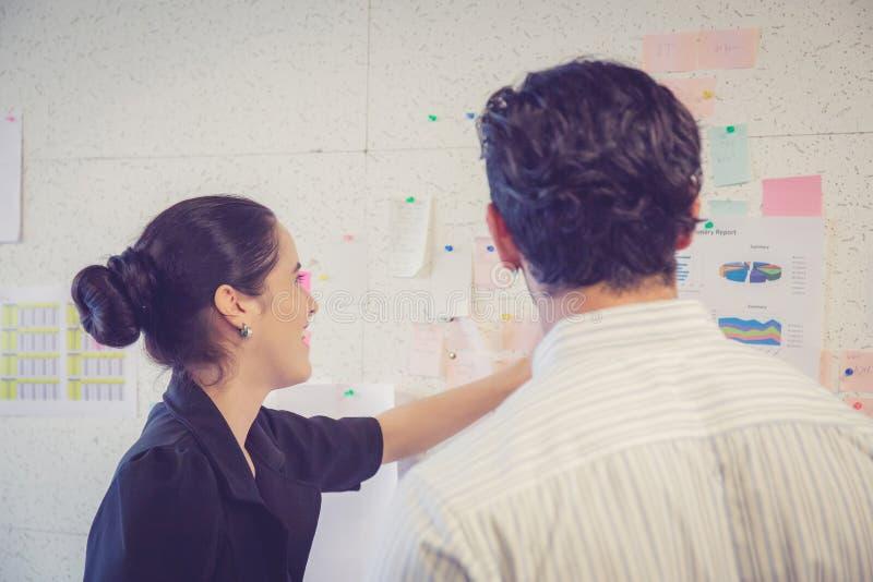 Jonge onderneemster met huidige winst en secretaresse terwijl het geven van presentatie in bureau stock afbeelding