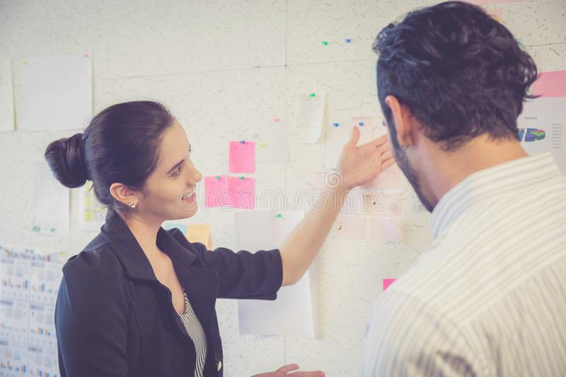 Jonge onderneemster met huidige winst en secretaresse terwijl het geven van presentatie in bureau stock fotografie