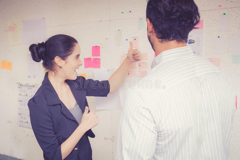 Jonge onderneemster met huidige winst en secretaresse terwijl het geven van presentatie in bureau stock afbeeldingen