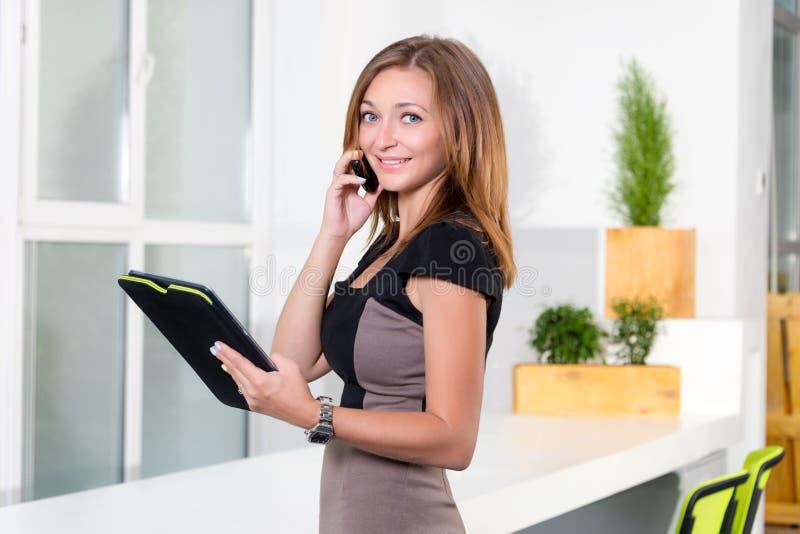 Jonge onderneemster in modern helder bureau die op de mobiele telefoon spreken en de tablet met een lijst van taken houden stock foto's