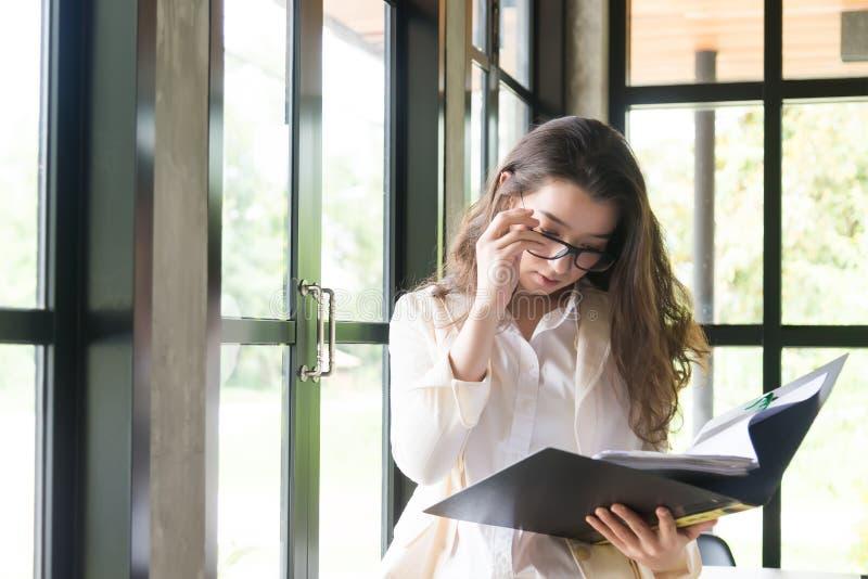 Jonge onderneemster op het werk en lezingsdocument in bureau bedrijfsvrouw die de documenten van de kostuumholding ter beschikkin stock foto's