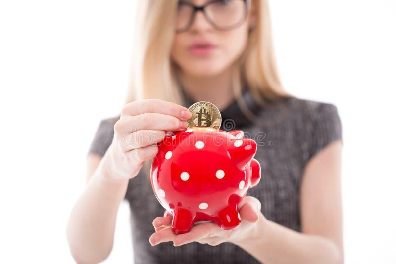 Jonge onderneemsterdaling bitcoin in geïsoleerd spaarvarken royalty-vrije stock fotografie