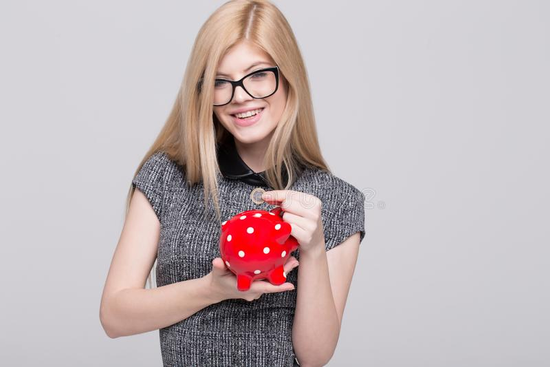 Jonge onderneemsterdaling 1 euro muntstuk in spaarvarken royalty-vrije stock foto