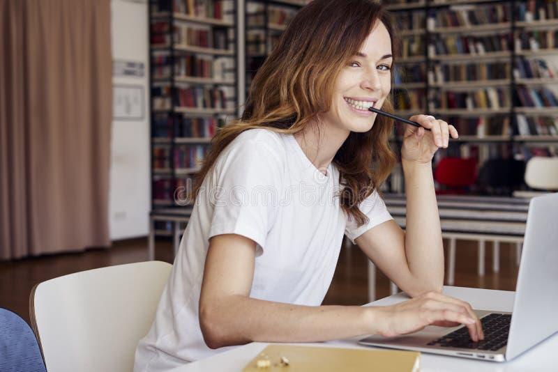 Jonge onderneemsterondernemer of universitaire student die aan laptop met boek op de wetenschappelijke thesis in een bibliotheek  royalty-vrije stock afbeelding