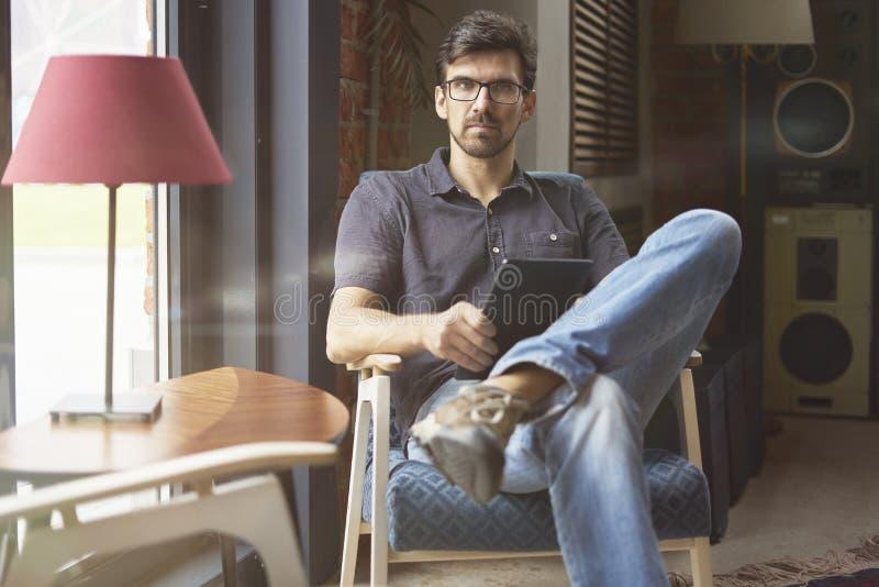 Jonge ondernemer die aan opstarten in modern bureau werken die digitale tablet gebruiken Mens die glazen en jeans, ernstig gezich royalty-vrije stock afbeelding
