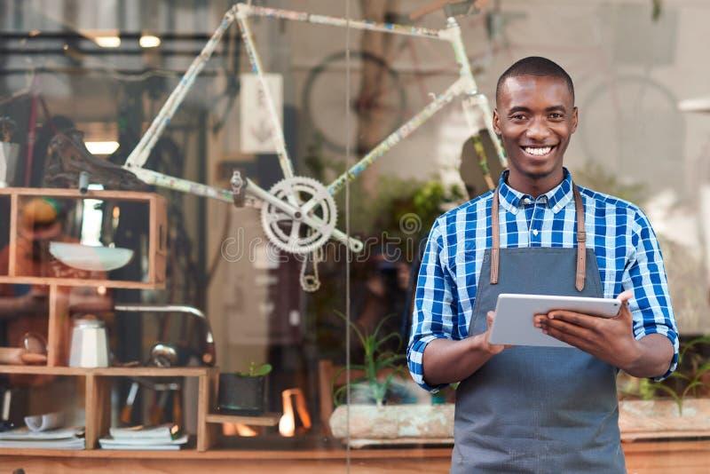 Jonge ondernemer die een tablet voor zijn koffie gebruiken royalty-vrije stock fotografie