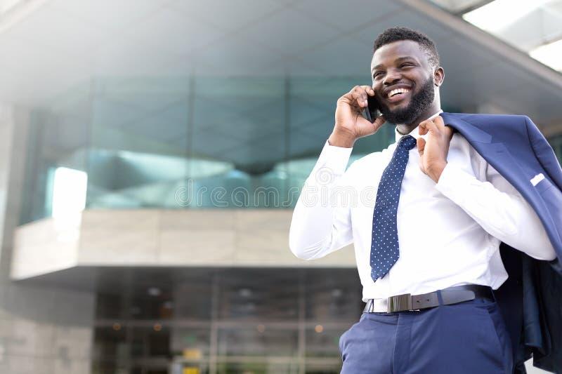 Jonge ondernemer die zich buiten het bureau bevinden en op de mobiele telefoon spreken De ruimte van het exemplaar royalty-vrije stock afbeeldingen