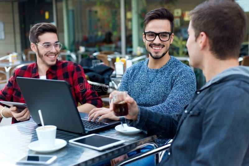 Jonge ondernemers die bij koffiebar werken stock afbeeldingen