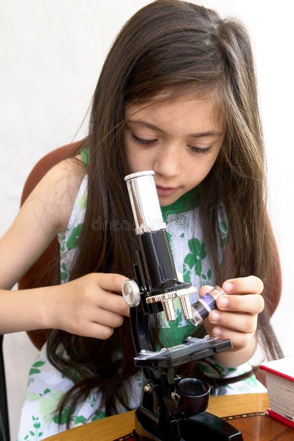 Jonge onderzoekersanalyses met een microscoop stock afbeeldingen