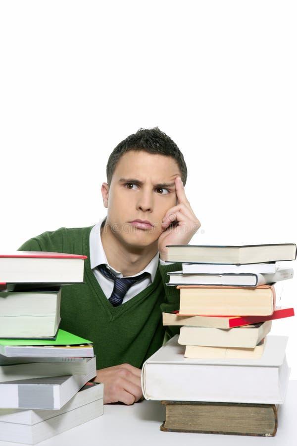 Jonge ongelukkige student met gestapelde boeken stock fotografie