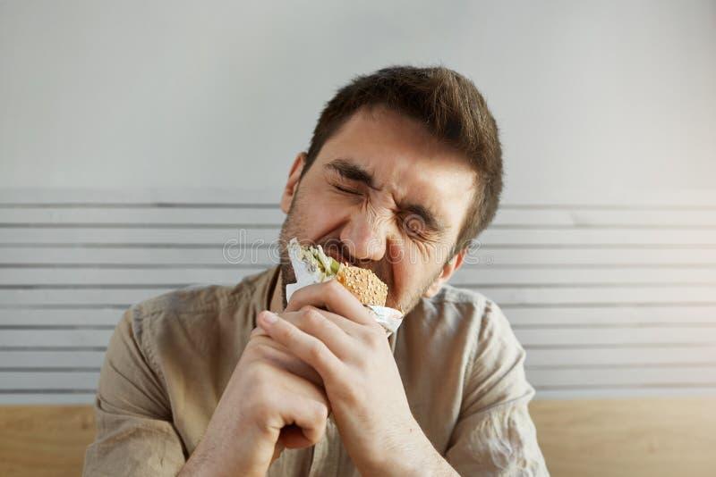 Jonge ongeschoren knappe kerel met donker haar die sandwich in snel voedsel met gesloten ogen, met gelukkig eten en tevreden stock fotografie