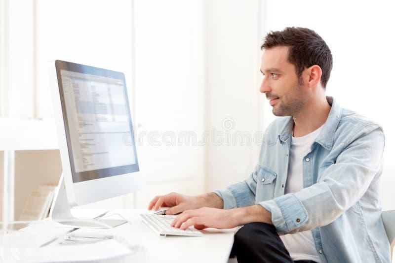 jonge ontspannen mens die computer met behulp van royalty-vrije stock afbeeldingen