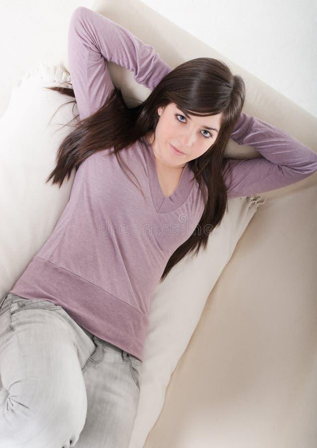 Jonge ontspannen vrouw het liggen op het binnenland van het laaghuis. royalty-vrije stock afbeelding