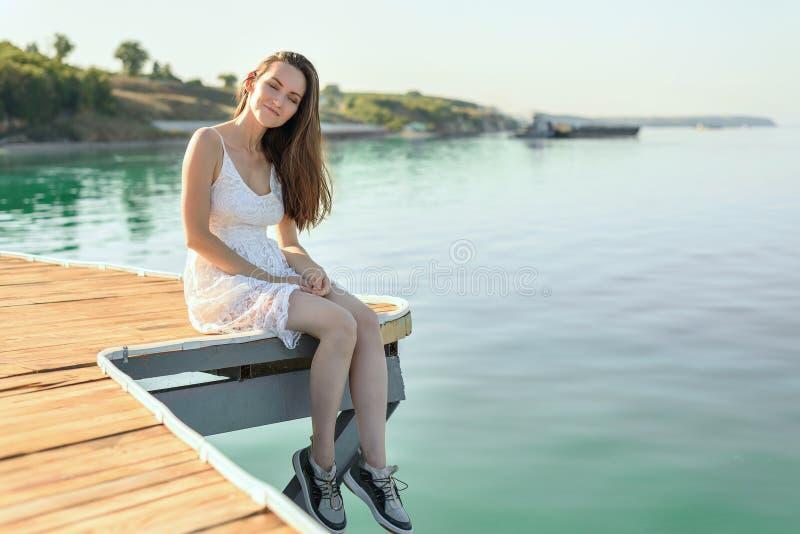 Jonge ontspannen vrouw in witte kledingszitting op een houten pijler op de achtergrond die van het overzees, bij zonsondergang va stock foto