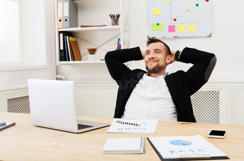 Jonge ontspannen zakenman met laptop in modern wit bureau royalty-vrije stock afbeelding