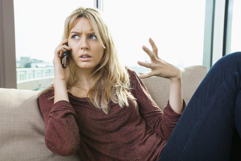 Jonge ontstemde vrouw die op mobiele telefoon thuis spreken royalty-vrije stock fotografie