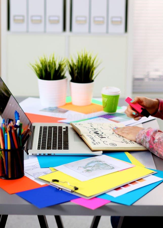 Jonge ontwerper die bij zijn bureau met een computer werken stock foto