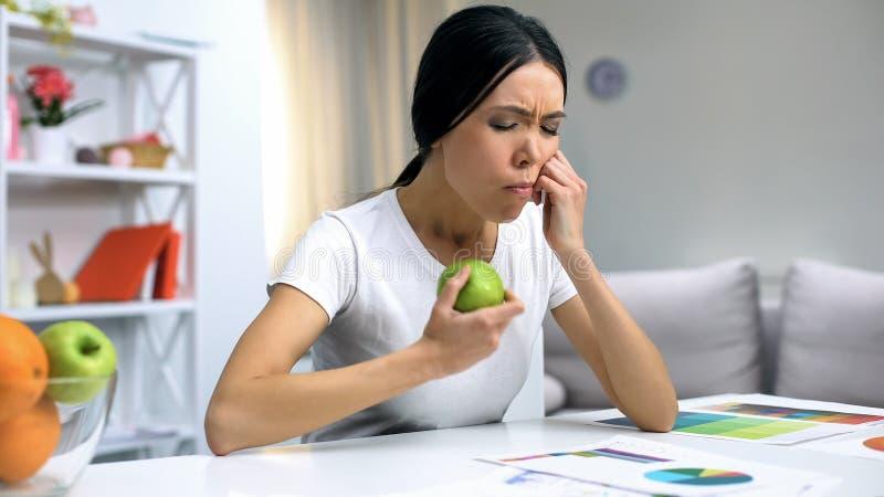 Jonge ontwerper die tandpijn voelen die groene appel houden, die gezondheid thuis werken stock foto's