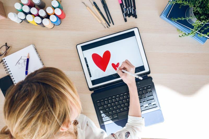 Jonge ontwerpervrouw die sommige harten met haar elektronische pen trekken op haar digitale tablet op het kantoor stock afbeeldingen