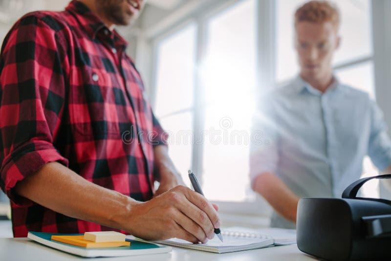 Jonge ontwikkelaars die in bureau samenwerken stock afbeeldingen