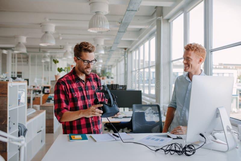 Jonge ontwikkelaars die virtuele werkelijkheidsglazen in bureau testen stock afbeeldingen