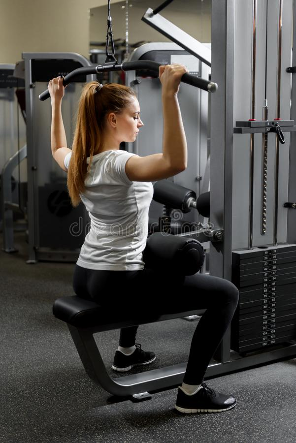 Jonge opgeleide meisje de bouwbicepsen in een gymnastiek stock afbeeldingen