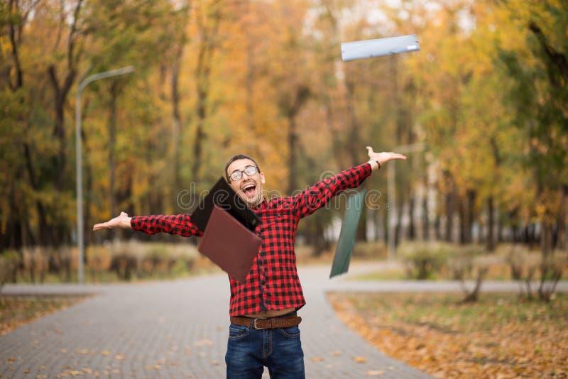Jonge opgewekte gelukkige student die examens overging Mens die handen opheffen stock foto