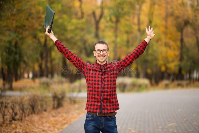 Jonge opgewekte gelukkige student die examens overging Mens die handen opheffen stock afbeeldingen