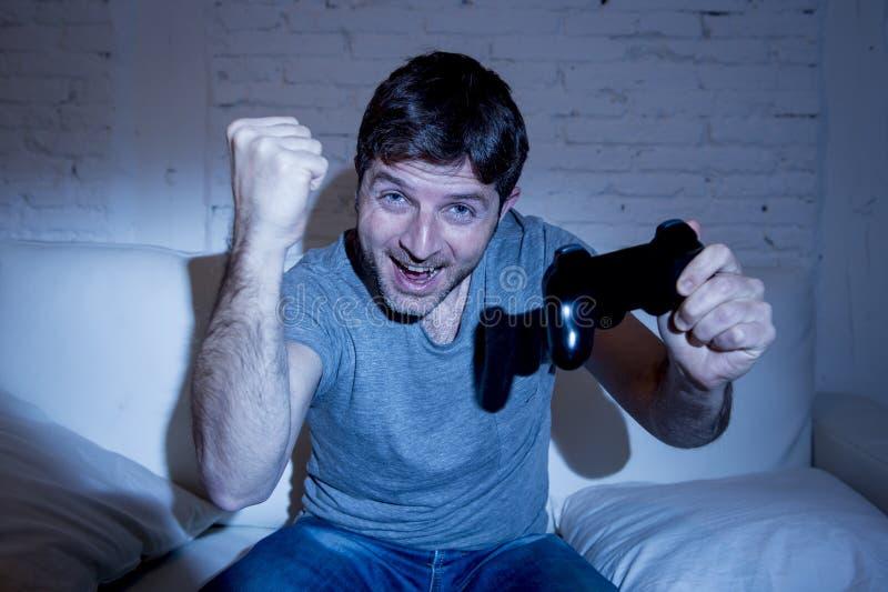 Jonge opgewekte mens die thuis op woonkamerbank het spelen videospelletjes zitten die afstandsbedieningbedieningshendel met behul royalty-vrije stock foto