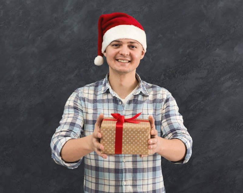 Jonge opgewekte mens in Kerstmanhoed met gift royalty-vrije stock afbeelding