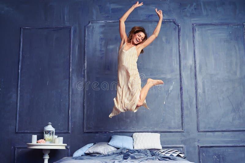 Jonge opgewekte vrouw die op bed springen royalty-vrije stock afbeelding