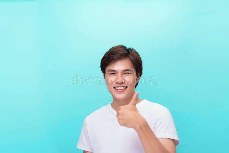 Jonge optimistische die mens op blauwe achtergrond wordt geïsoleerd die dreun met positieve emoties van inhoud en geluk tonen Con royalty-vrije stock afbeeldingen