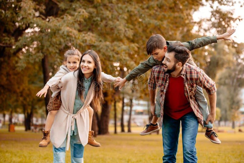 Jonge ouders die hun kinderen een vervoer per kangoeroewagenrit in geven royalty-vrije stock afbeeldingen