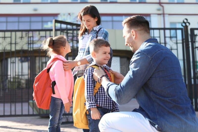 Jonge ouders die vaarwel aan hun kleine kinderen zeggen stock foto's